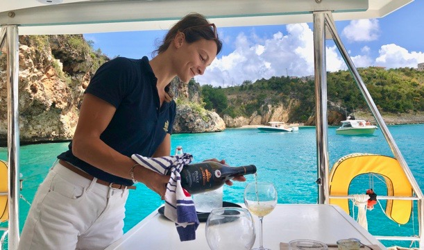 Pyratz Gourmet Sailing hostess serving a glass of white Burgundy wine to guests while the boat is anchored right in front of Little Bay.