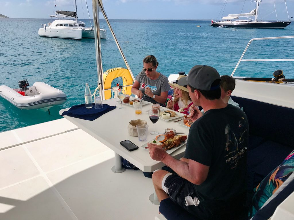 Parents and their two kids enjoying lobster, duck & fish for lunch on the turquoise water of Tintamarre.
