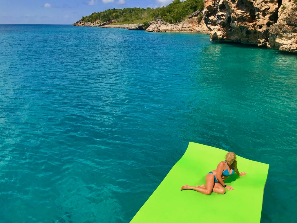 One of the guest lying on the floating mat, on the pristine water of Little Bay, facing the ocher cliffs.