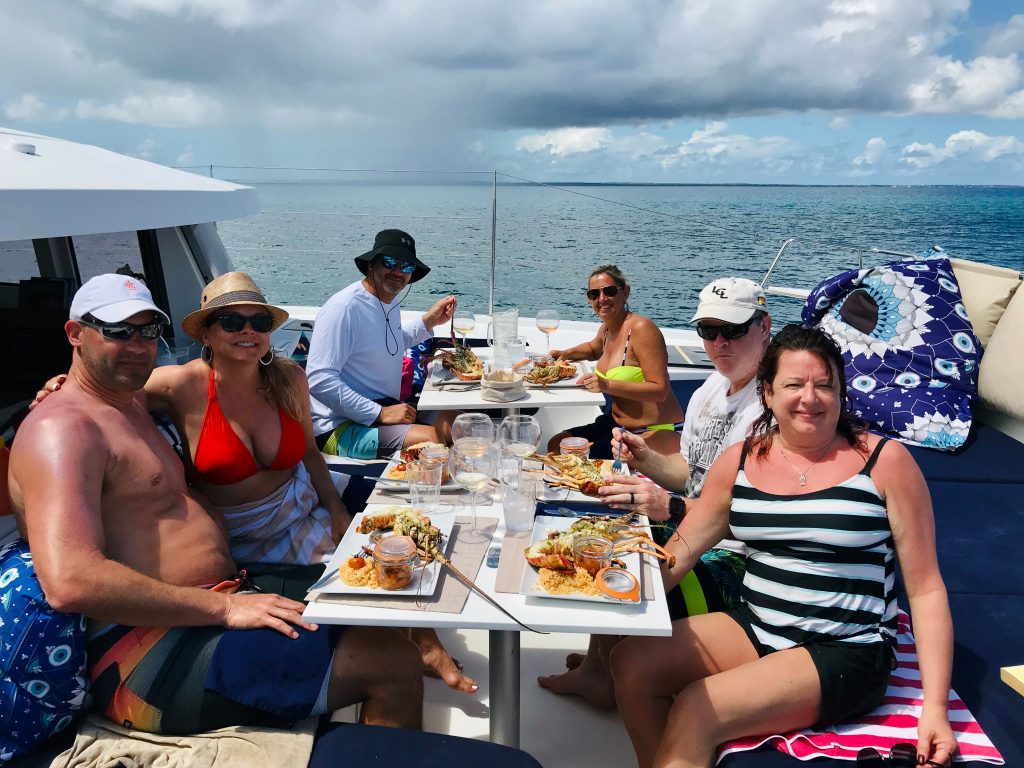 Gourp of friends having a gourmet lobster lunch on the bow deck of the catamaran, with plenty of rosé wine